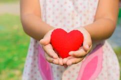Una niña se coloca con un corazón en sus manos que simbolizan el h Imagenes de archivo
