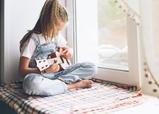 Una niña se está sentando por la ventana en la casa que toca la guitarra Foco selectivo El concepto de m?sica y de arte imágenes de archivo libres de regalías