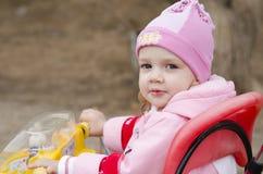 La niña mira en el marco que se sienta en la bici Imagenes de archivo