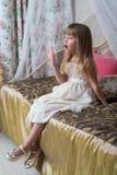 Una niña se sienta en una cama grande imagenes de archivo