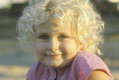 Una niña sonriente con el pelo rubio rizado, arboleda del jardín, CA Imagen de archivo