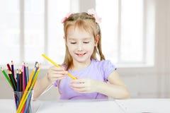 Una niña sostiene un lápiz y sonríe imágenes de archivo libres de regalías
