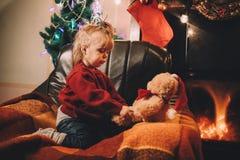 Una niña triste mira su oso de peluche querido Foto de archivo