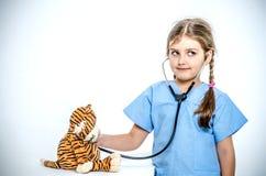 Una niña vestida en un traje quirúrgico escucha su tigre del juguete con un phonendoscope Imagen de archivo libre de regalías