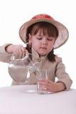 Una niña vierte el agua de un jarro en un vidrio Fotos de archivo
