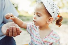 Una niña vierte la arena en su mano irreconocible del ½ s del ¿del fatherï El concepto del transience del tiempo y del hecho de q fotos de archivo libres de regalías