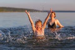 Una niña y su madre en el agua del mar Imágenes de archivo libres de regalías