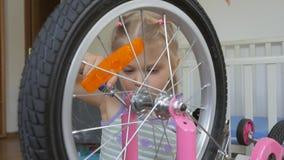 Una ni?a, bicicleta autorreparadora con un destornillador que se sienta en el cuarto de ni?os metrajes