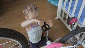 Una ni?a, bicicleta autorreparadora con un destornillador que se sienta en el cuarto de ni?os almacen de video