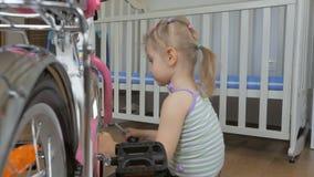 Una ni?a, bicicleta autorreparadora con un destornillador que se sienta en el cuarto de ni?os almacen de metraje de vídeo