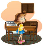 Una niña en la cocina que lleva una falda azul Fotografía de archivo