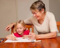 Una nin@era ayuda a una niña con el gráfico Imagenes de archivo