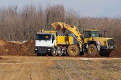 Una niveladora grande derrama la tierra y la piedra en el remolque de un camión de descargador pesado en el área de desarrollo  fotografía de archivo libre de regalías