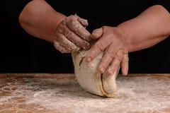 Una nonna della donna anziana sta impastando una pasta per la cottura del pane immagini stock