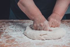 Una nonna della donna anziana sta impastando una pasta per la cottura del pane fotografia stock libera da diritti
