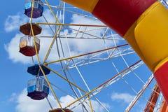 Una noria grande en un parque de atracciones en un fondo del cielo azul imagen de archivo