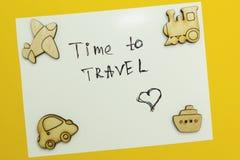 """Una nota """"tempo di viaggiare """"con il trasporto dipende un fondo giallo immagine stock libera da diritti"""
