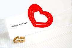 Una nota, anillos de bodas y un corazón rojo Imagenes de archivo