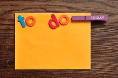 Una nota arancio con le parole da fare e un piolo con la parola venerdì Fotografie Stock Libere da Diritti