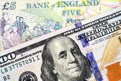 Una nota británica de cinco libras con cientos billetes de dólar americano fotografía de archivo