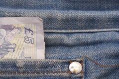 Una nota dalle cinque libbre in casella dei jeans. Fotografia Stock Libera da Diritti