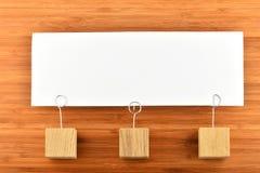 Una nota di carta con tre supporti isolati su fondo di legno Fotografia Stock Libera da Diritti