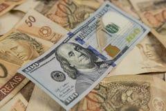 Una nota di 100 dollari sopra 50 note dei reais Immagini Stock Libere da Diritti