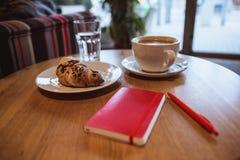 Una nota rossa e una penna rossa è sulla tavola in un caffè, in una tazza di caffè ed in un croissant su fondo immagini stock