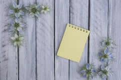 Una nota sobre una superficie de madera enmarcada por las flores 5 Fotos de archivo
