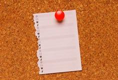 Una nota sobre una tarjeta del corcho Foto de archivo libre de regalías