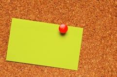 Una nota sobre una tarjeta del corcho Imagenes de archivo