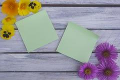 Una nota su una superficie di legno incorniciata dai fiori 7 di estate Fotografia Stock
