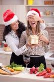 Una notte di Natale elegante moderna di due ragazze, in cucina con il regalo immagini stock libere da diritti