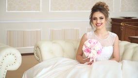 Una novia atractiva de la mujer joven con un ramo de flores se está sentando en el sofá en un cuarto lujoso Ella está esperando almacen de video