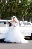 Una novia cerca del coche blanco largo de la boda Fotografía de archivo libre de regalías