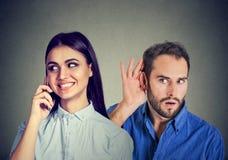 Una novia de engaño Hombre curioso que escucha secretamente una mujer feliz que habla en el teléfono móvil con su amante foto de archivo