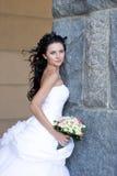 Una novia hermosa por la pared de piedra imagen de archivo libre de regalías