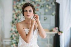 Una novia joven dulce el día de boda es que entra y que pone en los pendientes en su oído Muchacha morena hermosa con el pelo y Imágenes de archivo libres de regalías