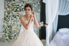 Una novia joven dulce el día de boda es que entra y que pone en los pendientes en su oído Muchacha morena hermosa con el pelo y Fotos de archivo libres de regalías