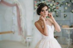 Una novia joven dulce el día de boda es que entra y que pone en los pendientes en su oído Muchacha morena hermosa con el pelo y Imagen de archivo libre de regalías