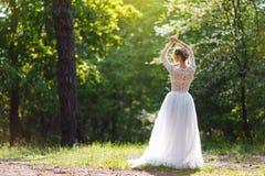 Una novia joven se coloca en el parque con ella detrás Bastante inusualmente presentando en cámara Fotos de archivo