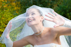 Una novia sonriente mira con el velo foto de archivo libre de regalías