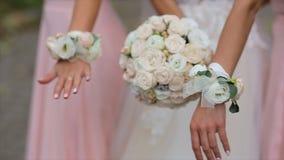 Una novia y damas de honor en los vestidos rosados que sostienen sus ramos almacen de metraje de vídeo