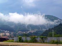 Una nube blanca descendió en el pueblo en el pie de una montaña boscosa fotos de archivo