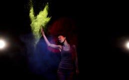 Una nube de colores rojos, amarillos y azules de Holi colgó sobre la muchacha Imagen de archivo libre de regalías