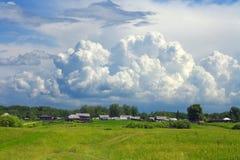 Una nube enorme sopra il piccolo villaggio Immagine Stock