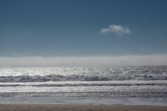 Una nube y ondas que alcanzan la orilla imagen de archivo