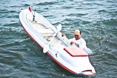 Una nuotata dell'uomo accanto alla canoa Fotografie Stock Libere da Diritti