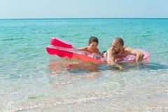 Una nuotata felice del figlio e del padre su un materasso gonfiabile un giorno di estate soleggiato fotografia stock