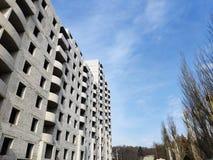Una nuova costruzione multipiana vuota del mattone leggero pronta per l'incarico contro un cielo blu fotografia stock